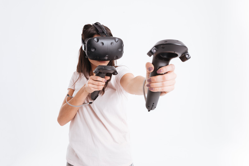 Someone wearing a virtual reality visor and interacting with the virtual world using joysticks
